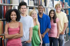 Six people in library standing by bookshelves Stock Photos