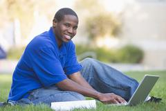 Man outdoors sitting on grass with laptop (selective focus) - stock photo