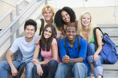 Six people sitting on staircase outdoors smiling Stock Photos