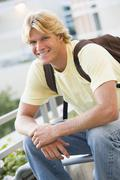 Man sitting outdoors on bench smiling (selective focus) Stock Photos