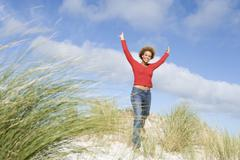 Young woman posing on a sand hill - stock photo