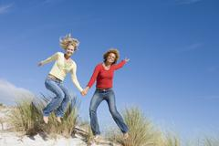 Young woman jumping on a sand hill - stock photo