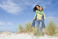 Young woman giving piggyback ride to her friend on a sand hill - stock photo
