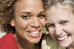 Two young women posing outdoors - stock photo