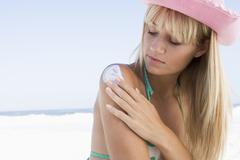 Woman on beach applying sunblock lotion to her shoulder - stock photo