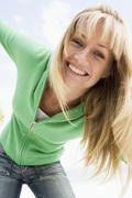 Blonde woman in a green sweater posing outdoors Stock Photos