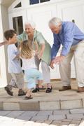 Grandparents welcoming grandchildren. Stock Photos