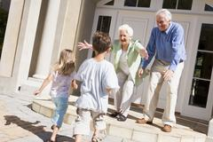 Grandparents welcoming grandchildren. Stock Photos