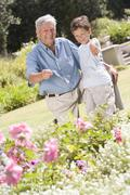 Grandfather and grandson outdoors in garden pointing at plants and smiling - stock photo