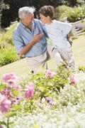 Grandfather and grandson outdoors in garden talking and smiling Stock Photos