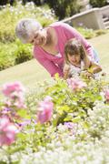 Grandmother and granddaughter outdoors in garden smiling Stock Photos