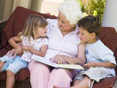 Grandmother reading to grandchildren. - stock photo