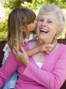 Grandmother getting a kiss from granddaughter. - stock photo