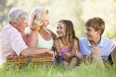 Grandparents having a picnic with grandchildren. - stock photo