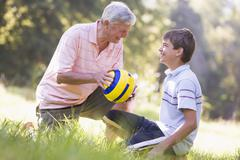Grandfather and grandson at a park with a ball smiling - stock photo