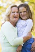 Grandmother and granddaughter outdoors and smiling - stock photo