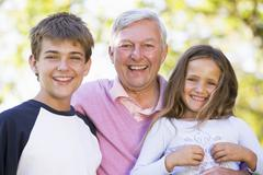Grandfather laughing with grandchildren. - stock photo