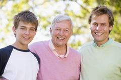 Grandfather with son and grandson smiling. - stock photo