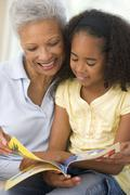 Grandmother and granddaughter reading and smiling Stock Photos