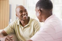 Two men in living room talking and smiling Stock Photos