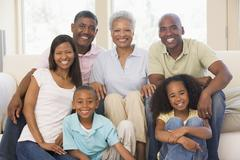 Extended family in living room smiling Stock Photos