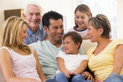 Extended family in living room smiling - stock photo