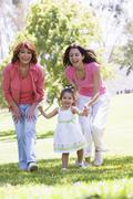 Grandmother with adult daughter and granddaughter in park Stock Photos