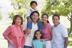 Extended family standing outdoors smiling Stock Photos