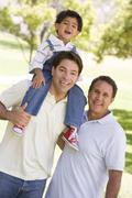 Grandfather with adult son and grandchild - stock photo