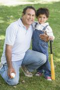 Grandfather and grandson holding baseball bat and smiling Stock Photos