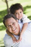 Grandfather piggryback riding grandson. Stock Photos