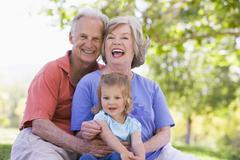 Grandparents with granddaughter in park - stock photo
