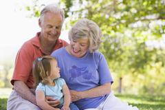 Grandparents with granddaughter in park Stock Photos
