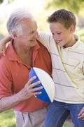 Grandfather and grandson outdoors with football smiling Stock Photos