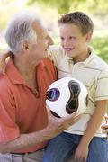 Grandfather and grandson outdoors with ball smiling Stock Photos
