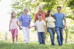 Extended family walking in park holding hands and smiling Stock Photos