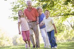 Grandparents walking with grandchildren. - stock photo