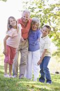 Grandparents laughing with grandchildren. - stock photo