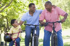 Grandfather grandson and son bike riding. - stock photo