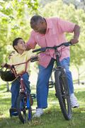 Grandfather and grandson on bikes outdoors smiling Stock Photos