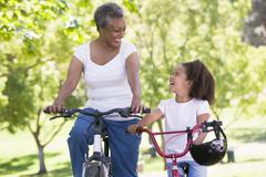 Grandmother and granddaughter on bikes outdoors smiling Stock Photos