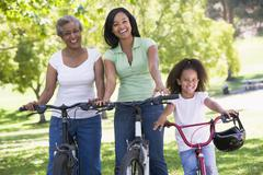 Grandmother with adult daughter and grandchild riding bikes Stock Photos