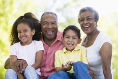 Grandparents laughing with grandchildren. Stock Photos