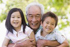 Grandfather posing with grandchildren. - stock photo