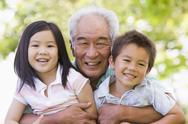 Stock Photo of Grandfather posing with grandchildren.