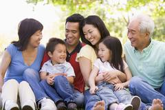Extended family sitting outdoors smiling - stock photo