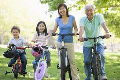 Grandparents bike riding with grandchildren. Stock Photos