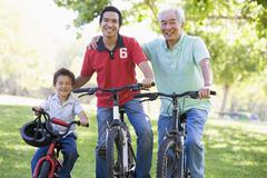 Grandfather son and grandson bike riding. - stock photo