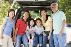 Extended family sitting in tailgate of car Stock Photos
