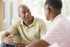 Two men in living room talking and smiling - stock photo